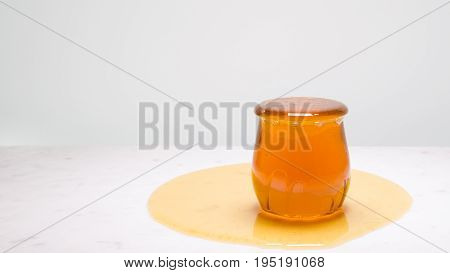 A jar overflowing with honey on a white marble countertop with copy space to the left. My cup runneth over.