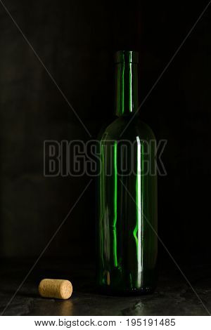 High wine glass made from green glass. No content. Glass and cork. Side view. Low key.