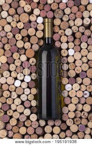 Bottle of white wine and corks on wooden table