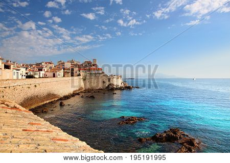 Seawall and buildings of old town Antibes harbor