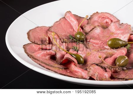 Plate of cold cuts with capers.Cutting meat on a plate with capers. Close up.