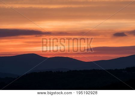 Bright Orange Cloudy Sky Above Mountain Ridges