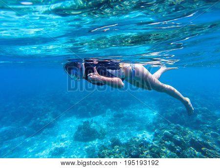 Woman snorkeling in blue water. Snorkel shows thumb in full face mask. Summer activity. Beautiful girl swims in sea. Underwater photo of oceanic landscape. Seaside adventure. Water sport in tropic sea