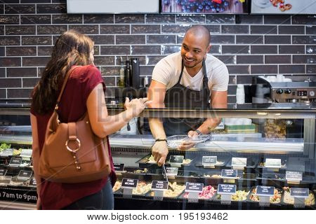African waiter serving fresh food to young woman. Happy smiling guy preparing take away salad for woman customer. Black man with apron taking pasta salad in spoon and serving to customer.