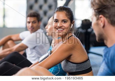 Happy young woman sitting on ground and exercising while listening to music. Smiling young woman resting and looking at camera. Portrait of a latin girl in fitness class listening to music.