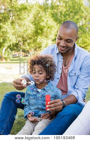 Smiling father and son playing with soap bubbles at park. Little african boy blowing soap bubble in park with dad. Black father and son playing together and sitting on grass.