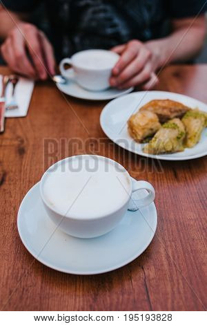 A man in a cafe eats coffee with a traditional oriental baklava dessert. Eastern food. Turkish dessert.