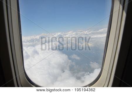 Plane window with blue sky and white clouds. Charter flight from Poland to Turkey.