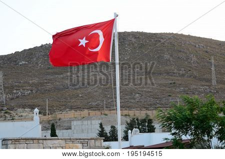 Turkish flag in Bagla holiday resort near Bodrum. Behind hills and buildings.
