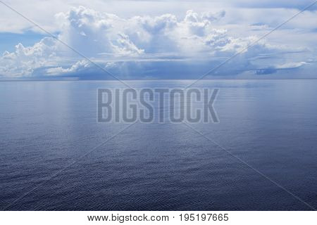Seaside landscape with still blue water and tropical island. Sea view with distant island. White fluffy clouds above ocean. Sea and sky minimal photo background. Summer travel relaxing panorama