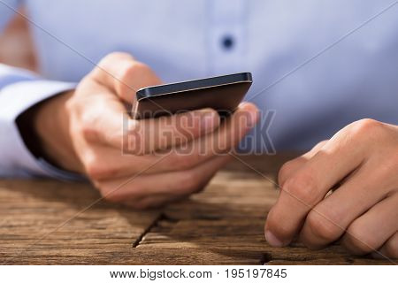 Close-up Of A Hand Using Smart Phone Over The Wooden Desk