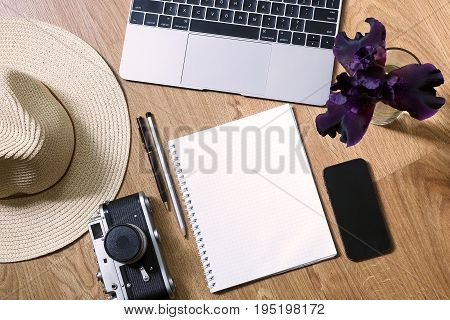Working space of the blogger before the vacation - a laptop a notebook a pen a pencil a phone a vintage camera a hat. Top view home office mockup. Blogger day. Flat lay.