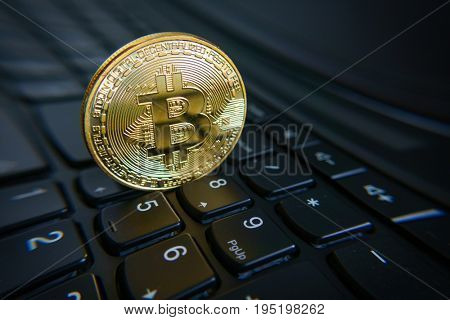 Golden bitcoin coin on the black laptop keyboard. Macro. Cryptocurrency concept