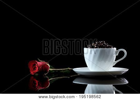Cup With Coffee Beans And Rose On A Black Reflective Background