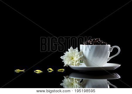Cup With Coffee Beans Anf White Chrysanthemum On A Black Reflective Background