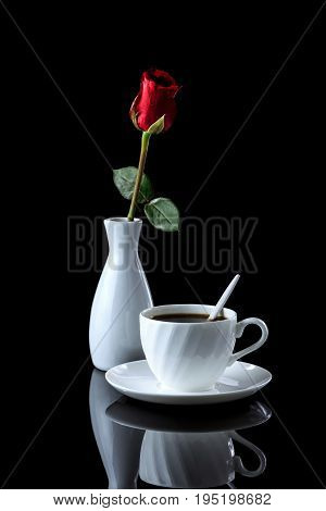 Composition With Cup Of Coffee And Rose On A Black Reflective Background