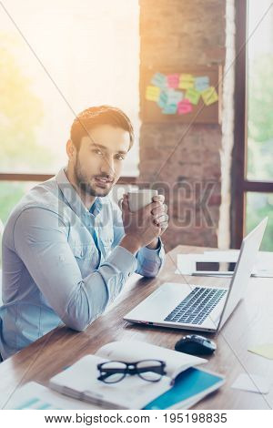 Young Dreaming Middle Eastern Bank Worker Is Thinking In Front Of Laptop At Work Place With The Cup