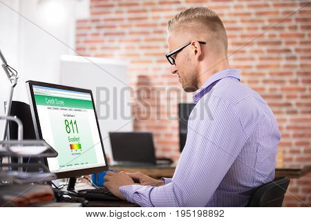 Young Businessman Checking Online Credit Score On Computer In Office