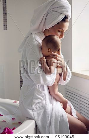 mother in a Bathrobe and towel on head sits on a round bathtub and holding a naked baby in her arms