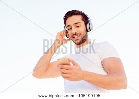 Smiling Muscular Young Brunet Is Enjoying Listenng To The Music In Modern Headphones, Isolated On Wh