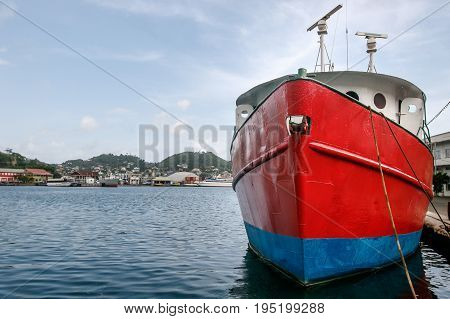 Red vessel in port, moored to the dock.
