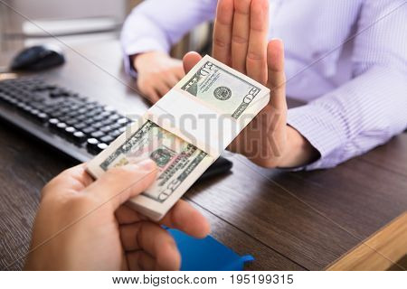 Cropped Hand Of Businessman Refusing To Take Bribe From Partner At Workplace