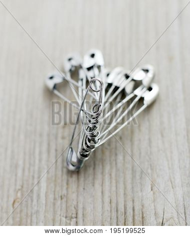 Sewing Safety Pin Macro On A Wood Background,
