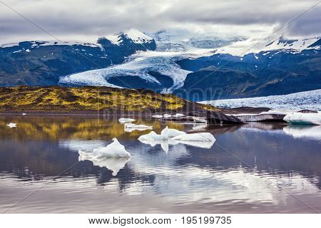 Summer in Iceland. The concept of extreme northern tourism. The colossal glacier Vatnajokull is melting at the edges, sliding to the ocean. Glacier meltwater form a picturesque lake