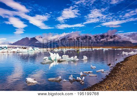 Cirrocumulus magically reflected in the water of lagoon. The concept of northern extreme tourism. The ice floes and cirrocumulus clouds of lagoon Jokulsarlon, Iceland