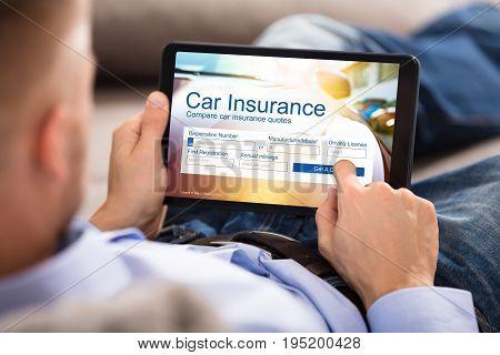 Close-up Of A Man Filling Car Insurance Form On Digital Tablet