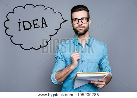 Idea imagination and inspiration concept. Nerdy academic professor genious is thoughtful in glasses holding a notebook and thinking about exams