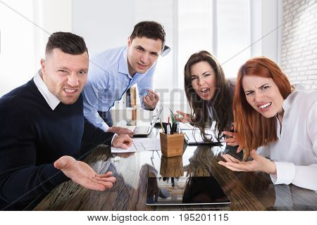 Group Of Business Executives Complaining Toward Camera In Office