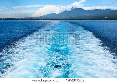 Sea ship tail and island landscape. Tropical islands ferry travel. Cruiseliner seawater trail. Deep ocean top view. Big ship pitching image. White water wave in the sea. Exotic island hopping