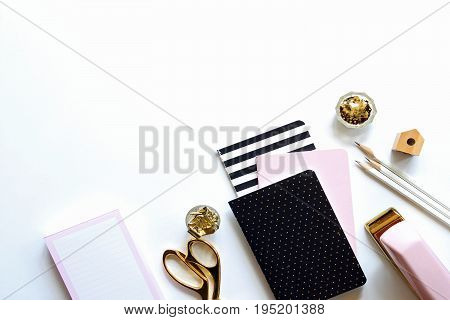 Chic pink, white, gold and black office supplies frame white background with copy space