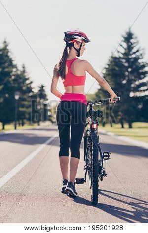 Fit Sportwoman Is Outside On A Summer Day Finished Cicling On Modern Bike, Walking With It, In Fashi