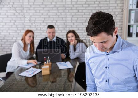 Portrait Of A Businessman With His Colleagues In Background At Office