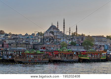 Istanbul Turkey - April 25 2017: Traditional fast food bobbing boats serving fish sandwiches at Eminonu district with Rustem Pasha Mosque and Suleymaniye Mosque in the background before sunset