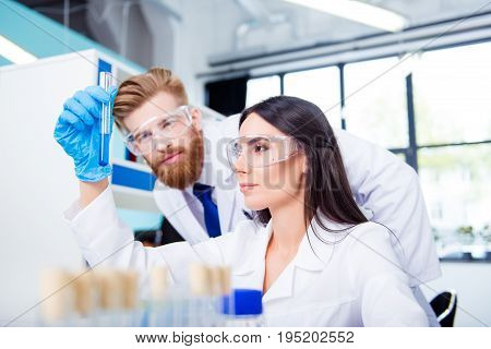 Team building concept. Young attractive and stylish interns (bearded man and beautiful girl) are collecting data for research in the lab. They are both in safety glasses and labcoats gloves