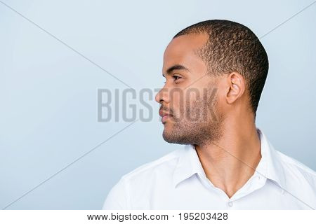 Closeup Side Photo Of African Business Man, Standing In White Formal Shirt On Pure Blue Background,