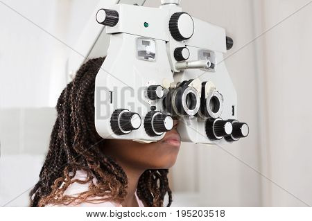 Close-up Of A Girl Doing Eye Test On Phoropter