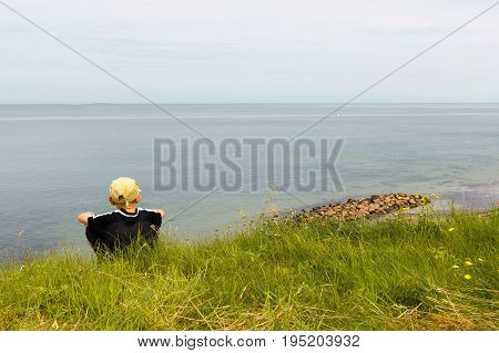 Boy sitting on te edge of a scarp high obove the sea Hundested Denmark July 10 2017