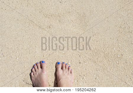 Female feet on white sand. Coral beach by sea. Sunny tropical seaside. Summer vacation in paradise banner template. Woman feet on white sand beach.Perfect day on exotic island background image
