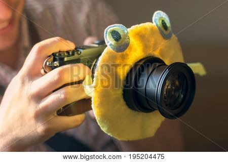 The digital DSLR camera in a hand with a children's toy on the camera lens to attract the child's attention. Male hands with camera take photo.