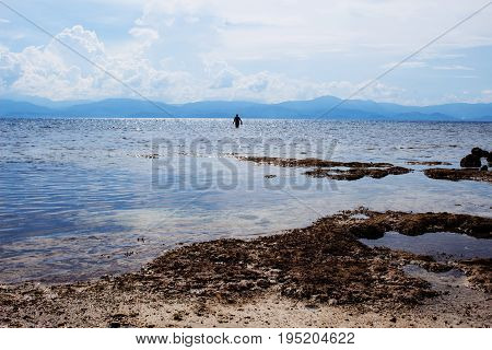 Sea landscape with man silhouette. Seascape with distant island. Tropical beach view with tourist. White sand beach with blue water. Sunny day on seaside. Secret beach still seawater. Holiday travel