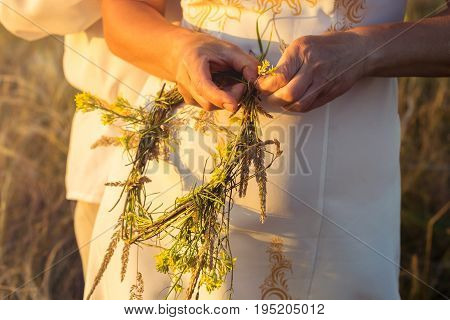 A girl in white traditional Slavic dress wreathes a wreath of fresh wildflowers at sunset. Russian traditions