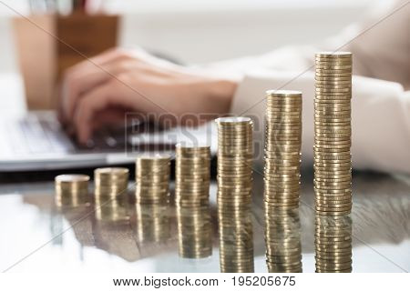 A Businessperson's Hand On Laptop With Stack Of Increasing Coins On Office Desk