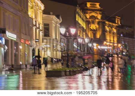 Abstract blurred background of people under umbrella walk on road in the city street in rain. Bright illumination and reflection in the wet pavement from shop windows and street lamps. Concept of Lifestyle of modern city, seasons, weather