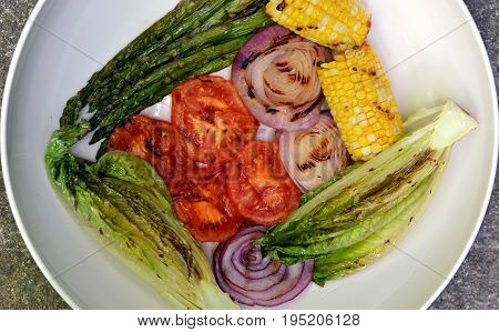 Grilled Vegetables shown in a white bowl: Close-up of sparagus, corn on the cob, Romaine lettuce, red onion and tomato.