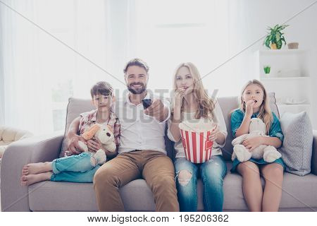 Fun Time Together. Happy Family Of Four Is Watching Interesting Educational Documentary, Eating Popc