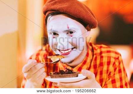 The Clown Is Eating A Cake In A Cafe And His Face Is Croaking.